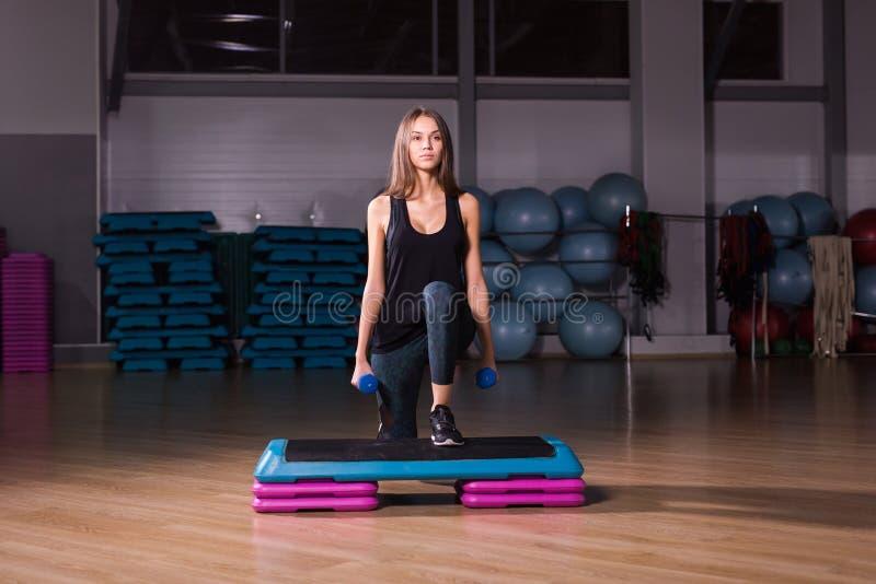 Aptitud, deporte, entrenamiento, gimnasio y concepto de la forma de vida - mujer que camina con pesas de gimnasia en la plataform imagen de archivo libre de regalías