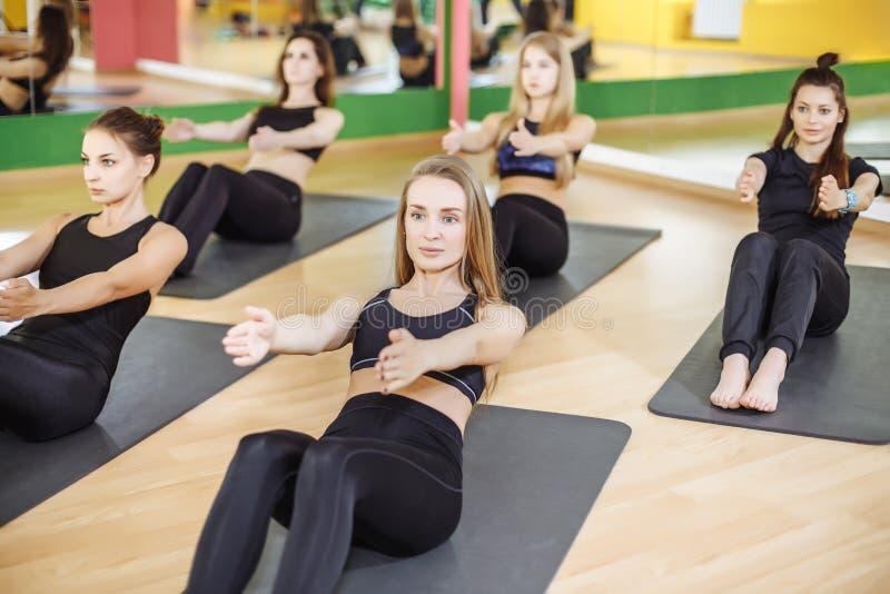 Aptitud, deporte, entrenamiento, gimnasio y concepto de la forma de vida - grupo de mujeres sonrientes que ejercitan en las ester fotografía de archivo