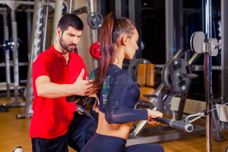 Aptitud, deporte, entrenamiento y concepto de la gente - mujer de ayuda del instructor personal que trabaja con en el gimnasio fotografía de archivo