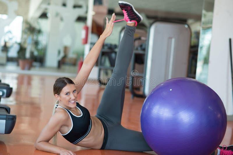Aptitud, deporte, entrenamiento y concepto de la gente - mujer sonriente que dobla los músculos abdominales con la bola del ejerc imagenes de archivo
