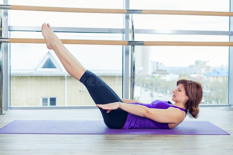 Aptitud, deporte, entrenamiento y concepto de la gente - mujer sonriente que hace ejercicios abdominales en la estera en gimnasio fotografía de archivo libre de regalías