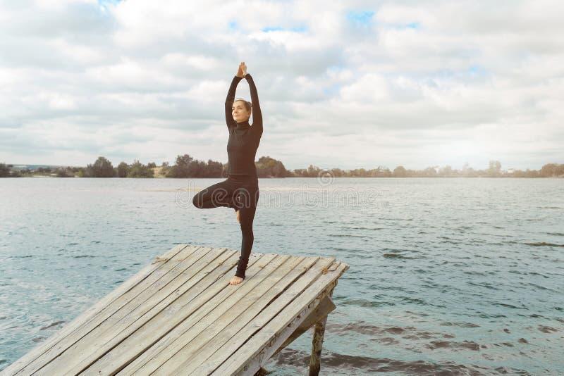 Aptitud, deporte, gente y concepto de la forma de vida - mujer joven que hace ejercicios de la yoga en la playa fotos de archivo