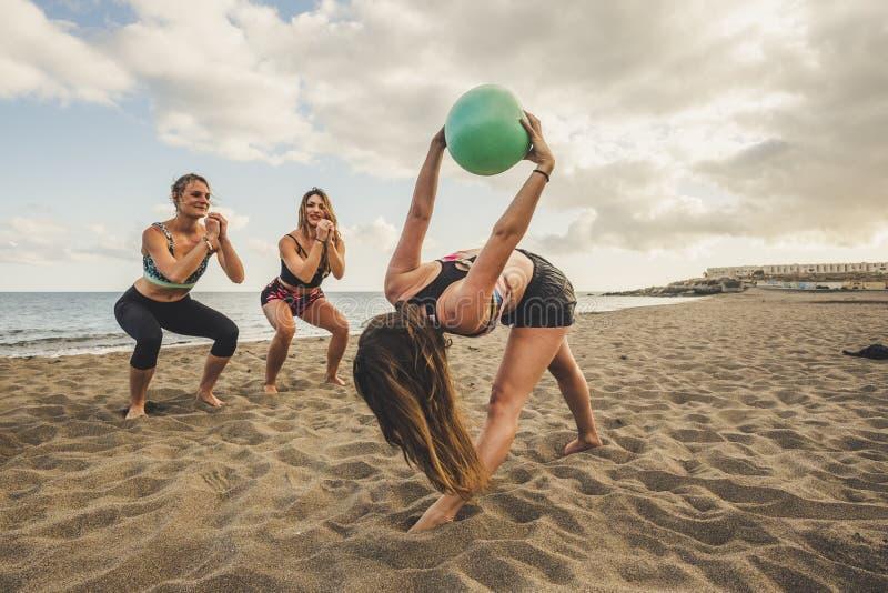 Aptitud, deporte, yoga y concepto sano de la forma de vida - grupo de personas que hace que los pilates presentan en la playa el  fotografía de archivo libre de regalías
