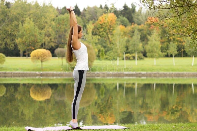 Aptitud, deporte, yoga y concepto sano de la forma de vida - mujer atractiva joven que estira sus brazos en la orilla en parque d fotos de archivo