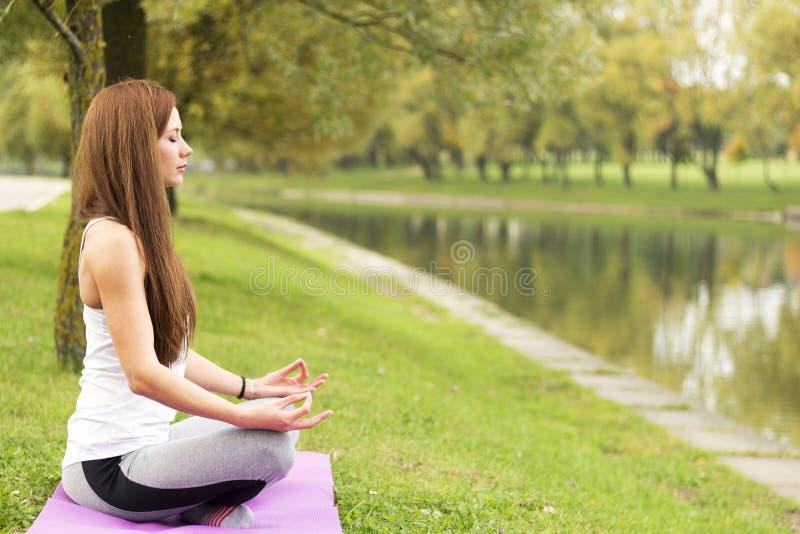 Aptitud, deporte, yoga y concepto sano de la forma de vida - mujer atractiva joven que medita en actitud del loto en costa del rí imagen de archivo libre de regalías