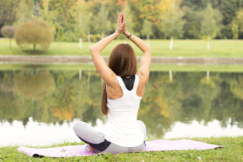 Aptitud, deporte, yoga y concepto sano de la forma de vida - mujer atractiva joven que medita en actitud del loto en costa del rí foto de archivo