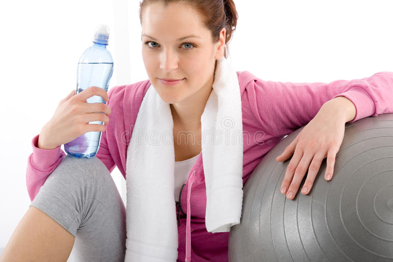 Aptitud - la mujer relaja la bola del ejercicio de la botella de agua imágenes de archivo libres de regalías