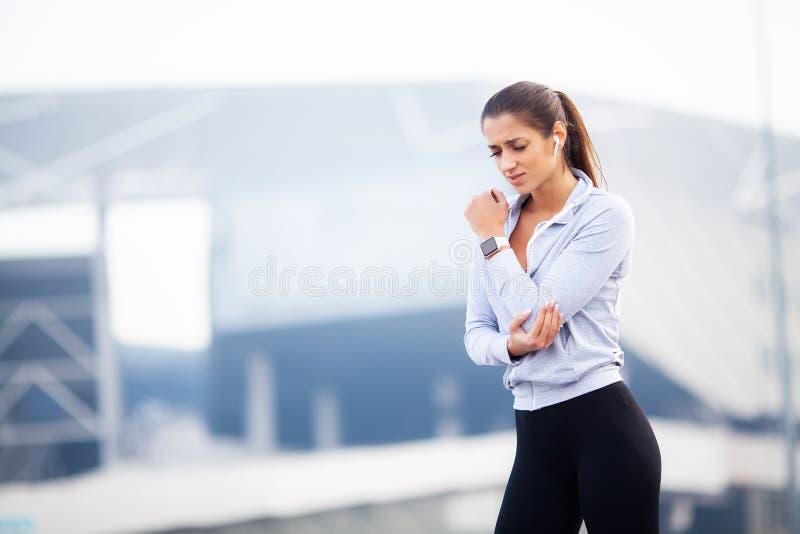 Aptitud La mujer tiene lesión y daño del accidente en los brazos mientras que entrenamiento en al aire libre, concepto del dolor  foto de archivo