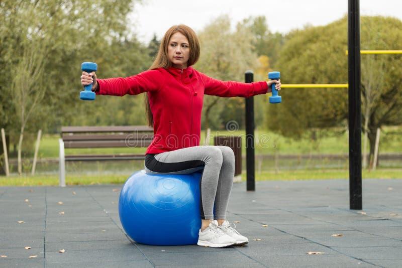 Aptitud, sana, aeróbicos, entrenamiento, mujer joven sonriente que hace ejercicio con la bola de los pilates en el patio del entr fotos de archivo libres de regalías