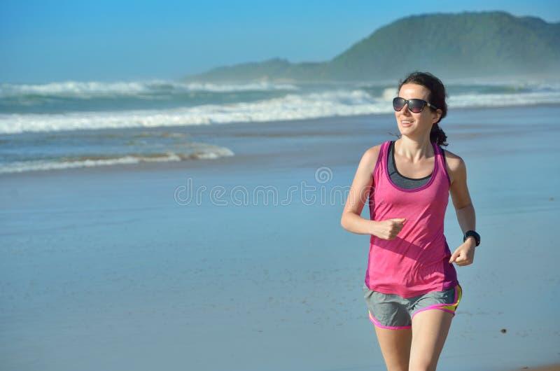 Aptitud y funcionamiento en la playa, el corredor feliz de la mujer que activa en la arena cerca del mar, la forma de vida sana y imagen de archivo libre de regalías
