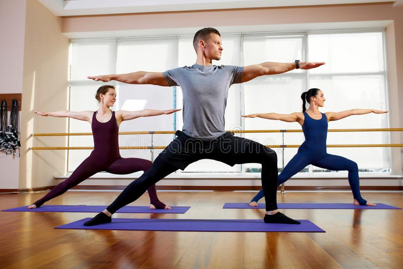 Aptitud, yoga y concepto sano de la forma de vida - grupo de personas que hace los ejercicios para estirar y meditar adentro imagenes de archivo