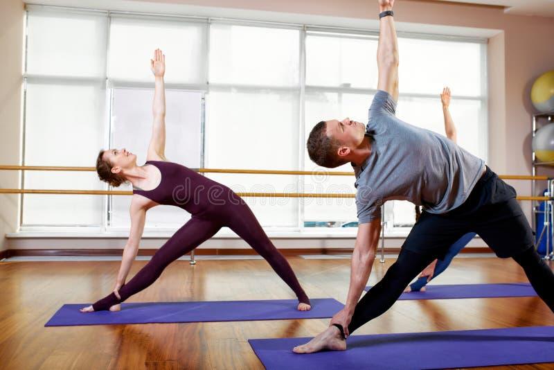 Aptitud, yoga y concepto sano de la forma de vida - grupo de personas que hace los ejercicios para estirar y meditar adentro imagen de archivo libre de regalías
