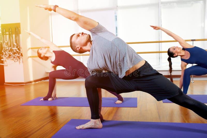 Aptitud, yoga y concepto sano de la forma de vida - grupo de personas que hace los ejercicios para estirar y meditar adentro fotografía de archivo