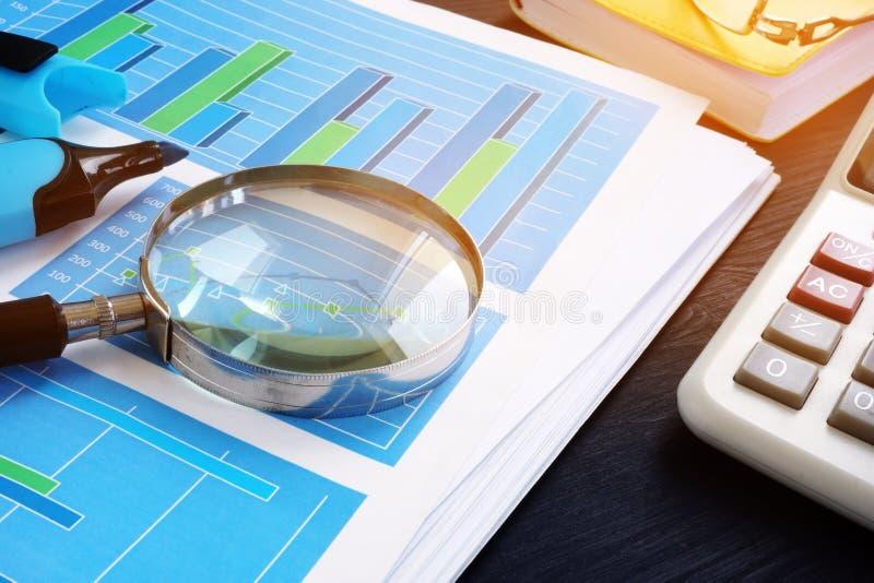 apurer Loupe sur les documents financiers avec des graphiques audit images libres de droits