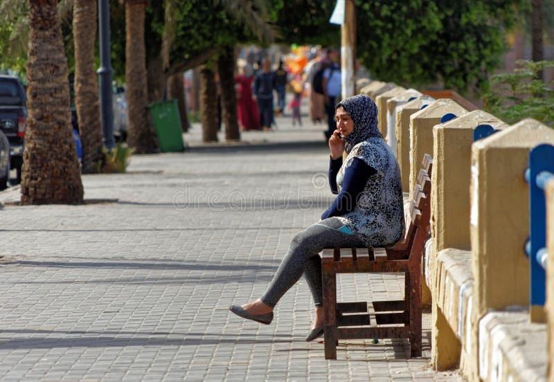 Aqaba, Jordânia, o 7 de março de 2018: Jovem mulher muçulmana que senta-se em um banco no passeio da praia de Aqaba que fala em s imagem de stock
