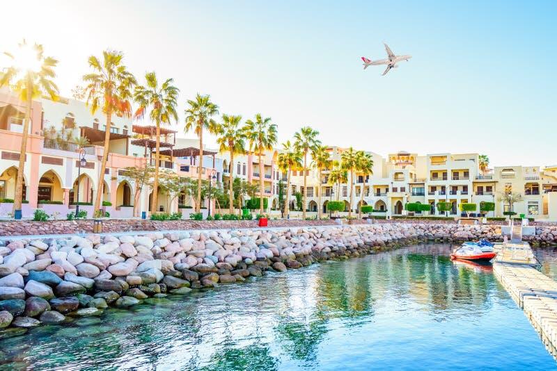 AQABA, JORDAN Avião branco de passageiros que sobrevoam o porto de Aqaba, situado no mar Vermelho fotos de stock