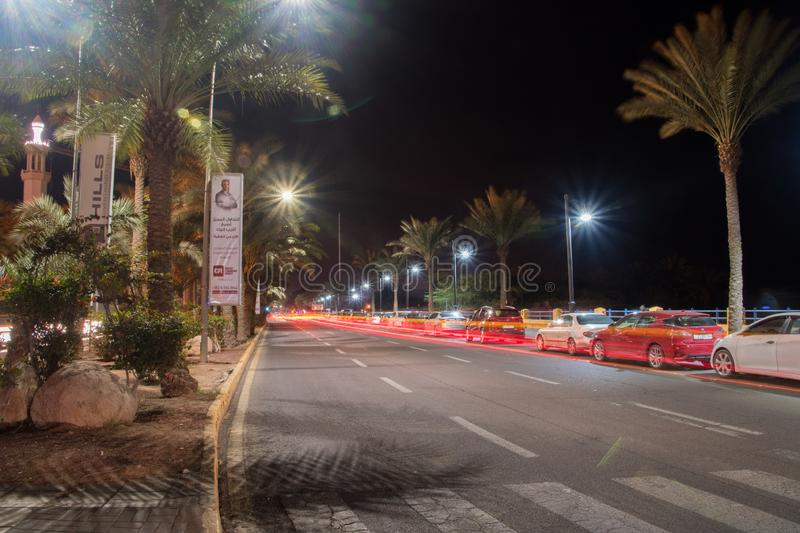 Red car light trails at night in K. Hussein street at Aqaba city. Aqaba, Jordan - February 8, 2019: Red car light trails at night in K. Hussein street at Aqaba royalty free stock images