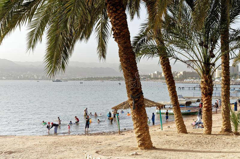 Aqaba, Jordan, March 8, 2018: Aqaba beach with fully clothed people bathing, palms in the foreground and the Israeli port of Eilat. In the background, middle royalty free stock image