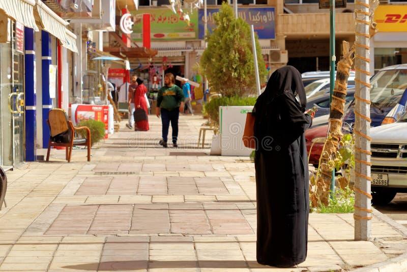 Aqaba, Jordanië, 7 Maart, 2018: Straatscène van een voorstad van Aqaba met een versluierde dame die haar mobiele telefoon met beh royalty-vrije stock fotografie