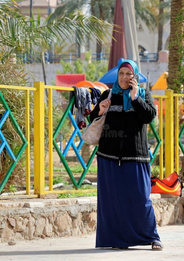 Aqaba, Jordania, el 7 de marzo de 2018: Mujer musulmán de mediana edad que se coloca en su teléfono móvil, riéndose del mismo tie imagenes de archivo