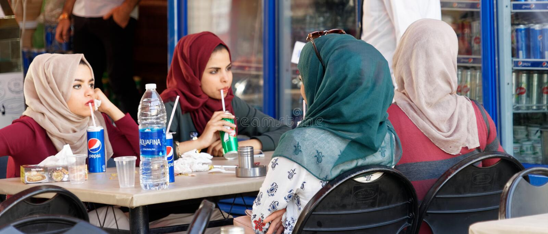 Aqaba, Jordanie, le 7 mars 2018 : Les jeunes dames détendent avec des boissons non alcoolisées dans un restaurant de rue au solei photos stock