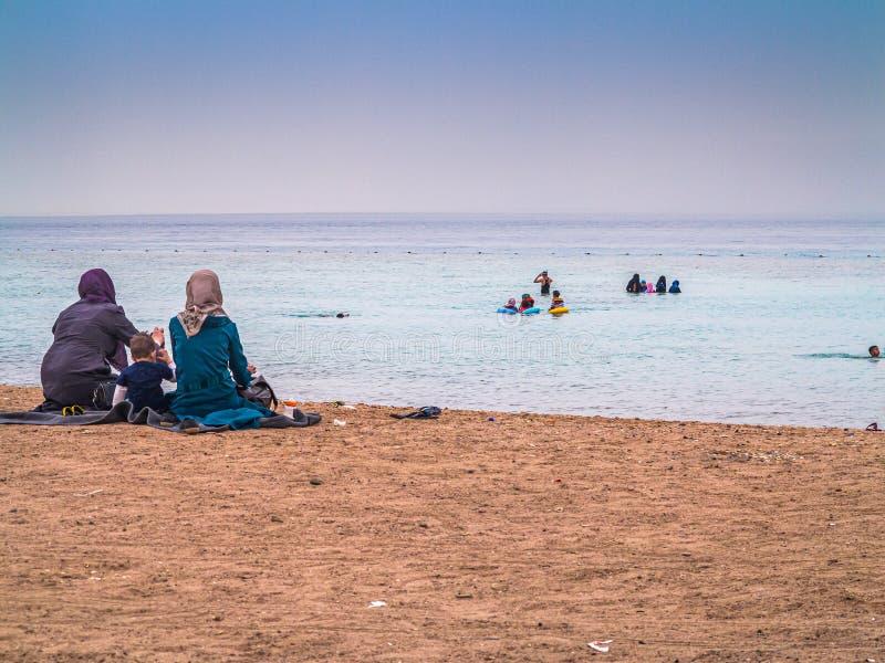 Aqaba, Jordanien - 11. April 2016 Frau in der moslemischen Kleiderschwimmen im Roten Meer im Sonnenuntergang lizenzfreie stockbilder