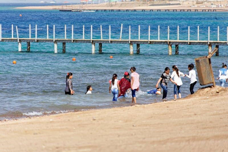 Aqaba Jordanien, mars 7, 2018: Barn på stranden av Aqaba som fullständigt är iklädd badningen och spela för hav arkivbilder