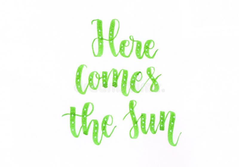 Aquí viene el Sun - mano verde que pone letras a la inscripción en verde con los puntos blancos stock de ilustración