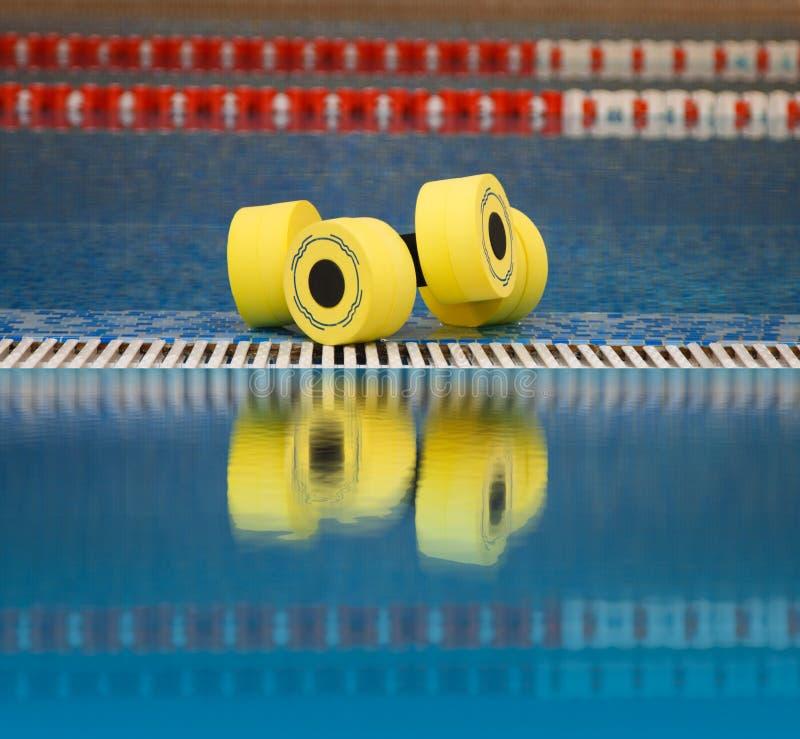 Aqua aerobics dumbbells reflected in water. Floating aqua aerobics dumbbells in swimming pool reflected in water stock photos
