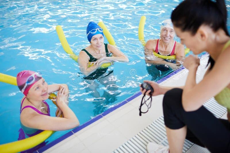 Aqua Aerobics Training. High angle portrait of three mature women doing aqua aerobics in swimming pool with female instructor, copy space stock photo