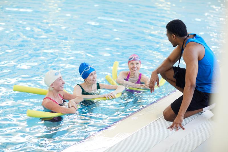 Aqua Aerobics Workout. Portrait of three mature women doing aqua aerobics in swimming pool with African-American fitness instructor, copy space stock images