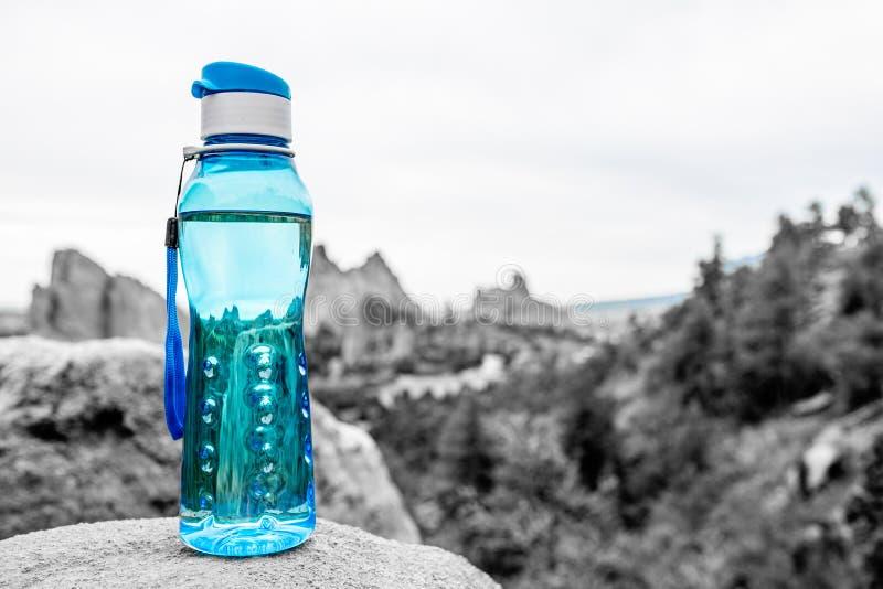 Aqua Blue Fitness Water Bottle med berg i bakgrund royaltyfria foton