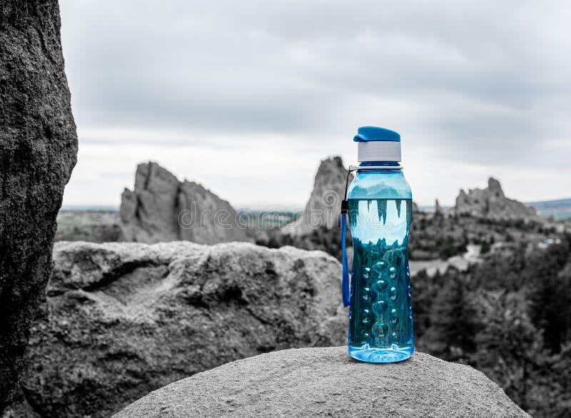 Aqua Blue Fitness Water Bottle med berg i bakgrund royaltyfri foto