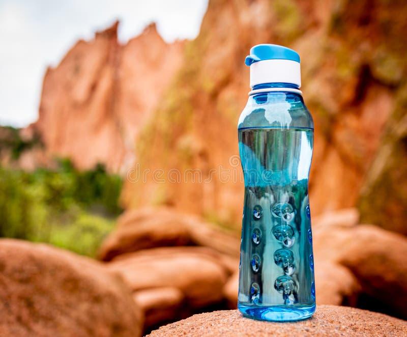 Aqua Blue Fitness Water Bottle med berg i bakgrund arkivfoto