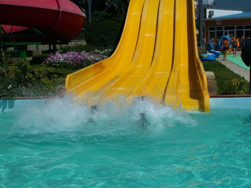 Aqua park fun. A yellow slide in aqua park, a person has just fallen into the pool royalty free stock photos