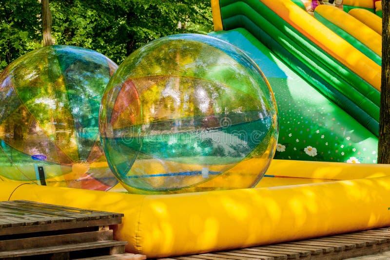 Aqua que zorbing Bolas de passeio da água colorida Atividade de água para crianças Crianças que jogam junto e que têm o divertime foto de stock