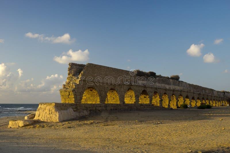 Aquaeductus romano da idade em Caesarea no por do sol foto de stock