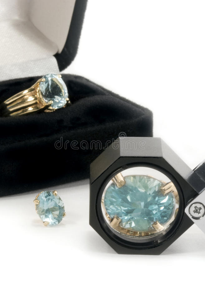 Aquamarine Jewelery & Loupe. Concept for inspecting gemstones with jewelers loupe. Aquamarine gemstones in ring and earring settings, one stone magnified by royalty free stock image