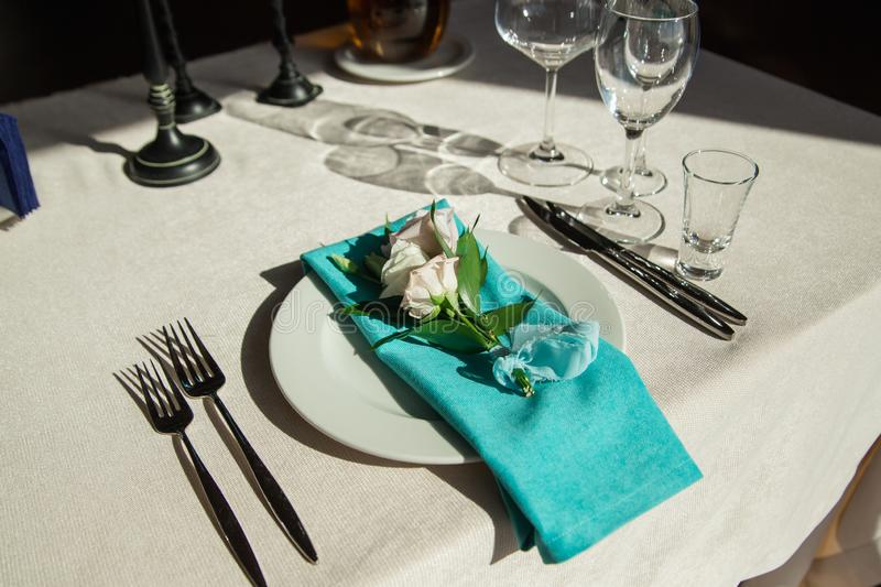 Aquamarine serviette with flower decor lying on the dinner plate. Aquamarine serviette with rose flower decor lying on the dinner plate. Hard light stock photos