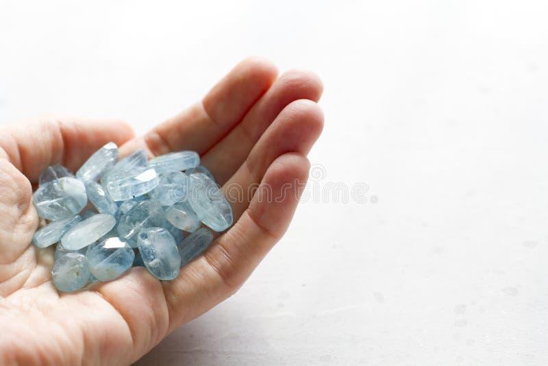 Aquamariner Stein liegt in der Hand Naturstein-Aquamarin auf einem wei?en Hintergrund Weibliche Hand kopieren Sie Platz f?r Ihren stockbild