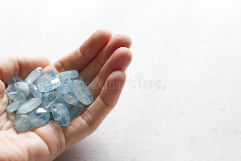 Aquamariner Stein liegt in der Hand Naturstein-Aquamarin auf einem wei?en Hintergrund Weibliche Hand kopieren Sie Platz f?r Ihren lizenzfreies stockfoto