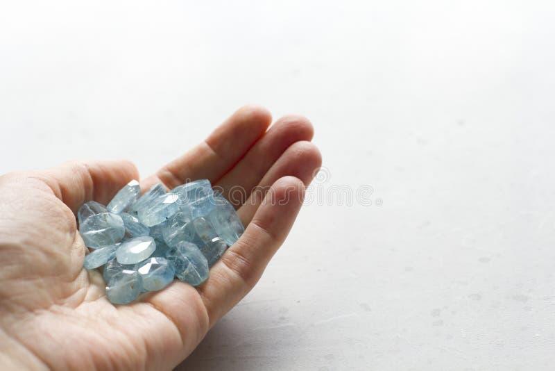 Aquamariner Stein liegt in der Hand Naturstein-Aquamarin auf einem wei?en Hintergrund Weibliche Hand kopieren Sie Platz f?r Ihren stockfotografie