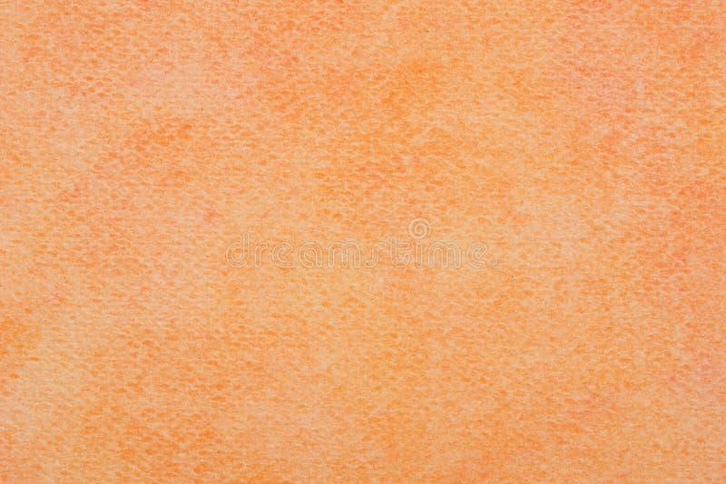 Aquarela alaranjada pintada no macro da textura do fundo do papel imagens de stock