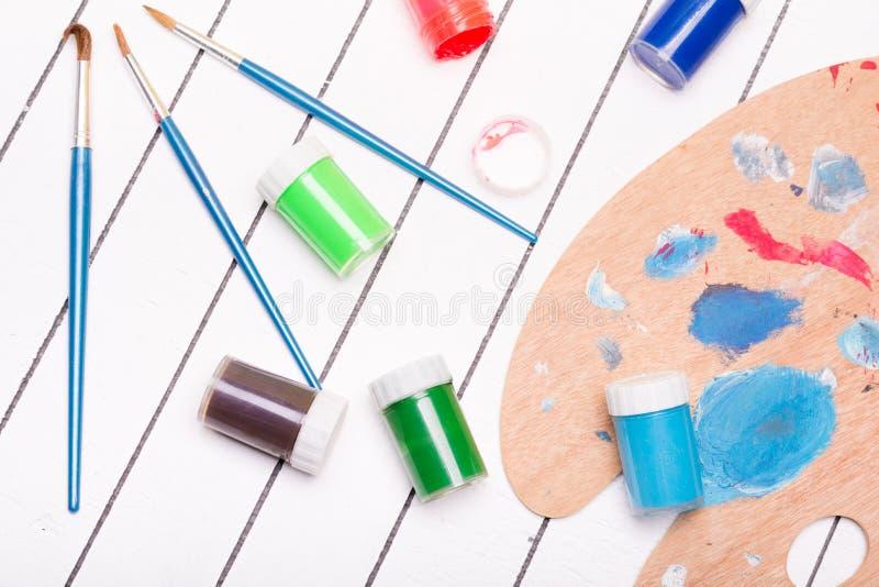 Aquarela e pintura à têmpera com as escovas de pintura diferentes em um fundo de madeira branco imagens de stock