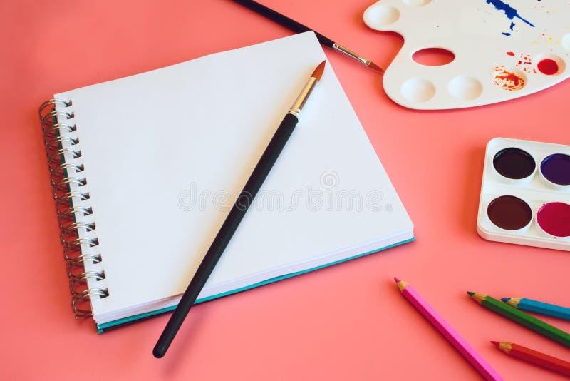 Aquarela, lápis coloridos e bloco de desenho com uma página vazia no fundo cor-de-rosa imagem de stock