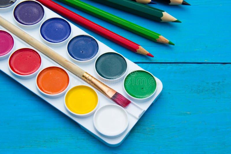 Aquarelles et crayons sur le fond en bois bleu images stock
