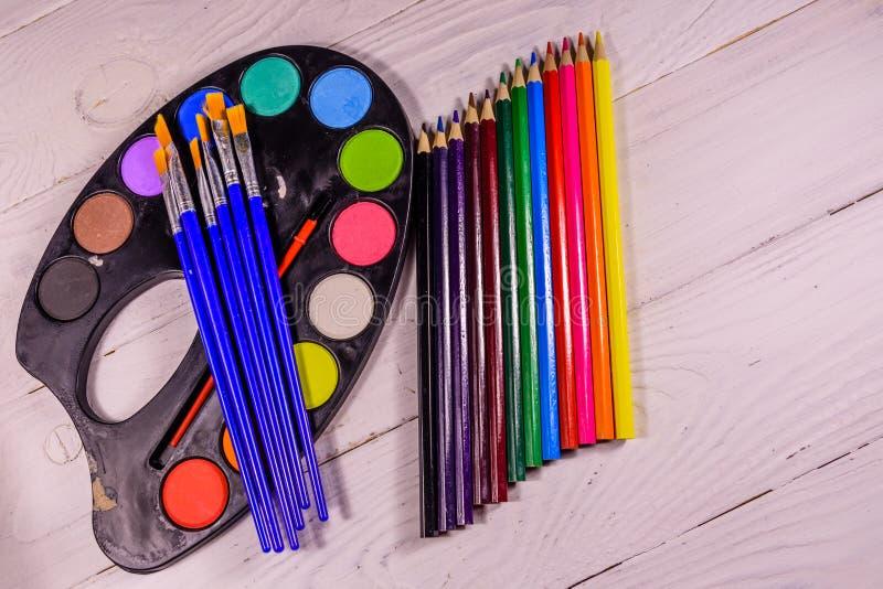 Aquarellfarben und -Pinsel auf Holztisch Beschneidungspfad eingeschlossen lizenzfreie stockbilder