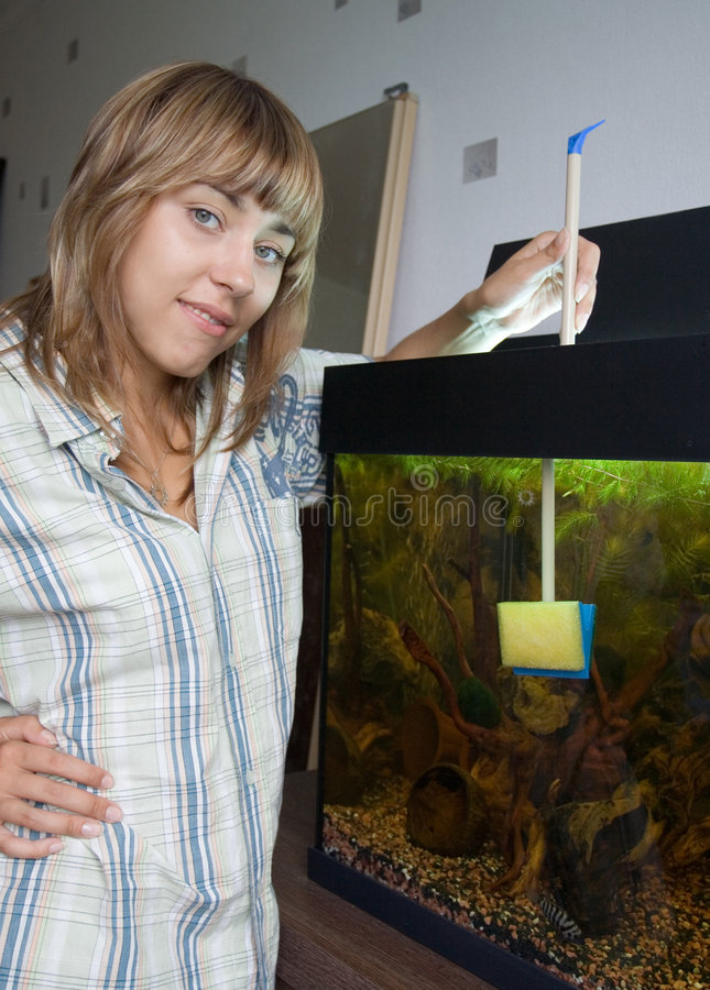 Aquarium de nettoyage de fille photo libre de droits