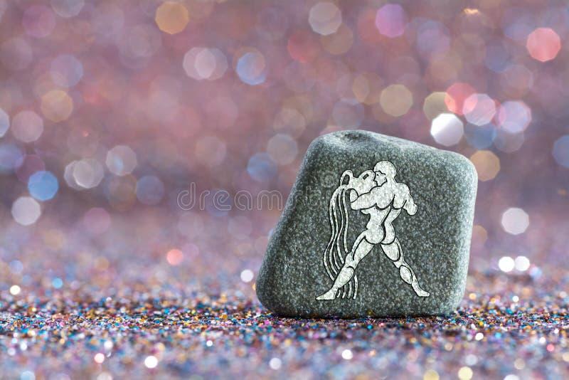 Aquarius zodiac sign. A green stone with Aquarius zodiac sign on glitter boke light background royalty free stock photo