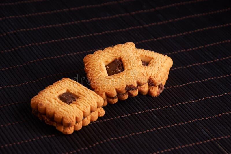 Aqueça as cookies caseiros de Gingersnap cobertas com chocolate no fundo vermelho do estilo imagem de stock royalty free